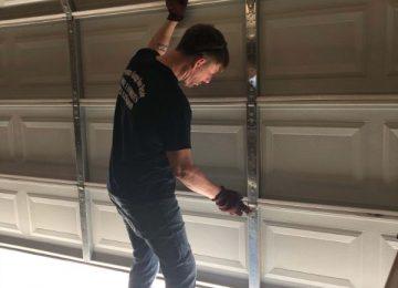Employee installing garage door